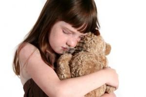 girl hugs teddy bear